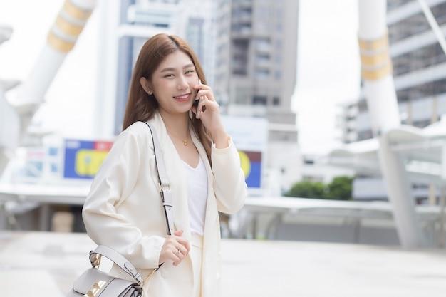Młody azjatycki biznes kobieta w białym garniturze uśmiecha się i trzyma mówić smartphone w jej ręce w dzień roboczy szczęśliwie w wielkim mieście z budynkami biznesowymi z miastem jako tło.