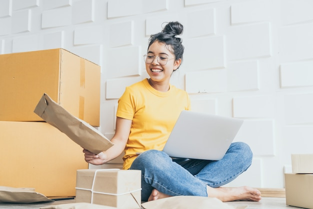 Młody azjatycki biznes zakłada właściciela sprzedawcy online za pomocą komputera do sprawdzania zamówień klientów za pośrednictwem poczty elektronicznej lub strony internetowej i przygotowywania paczek