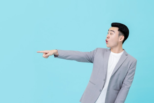Młody azjatycki biznesmen patrzeje zaskakujący podczas gdy wskazujący rękę kopiować przestrzeń