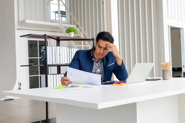 Młody azjatycki biznesmen patrzy na złe wyniki finansowe firmy.