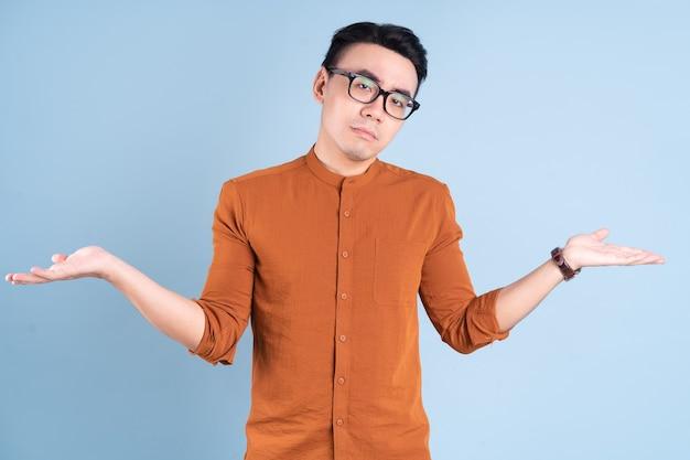 Młody azjatycki biznesmen pozuje na niebieskim tle