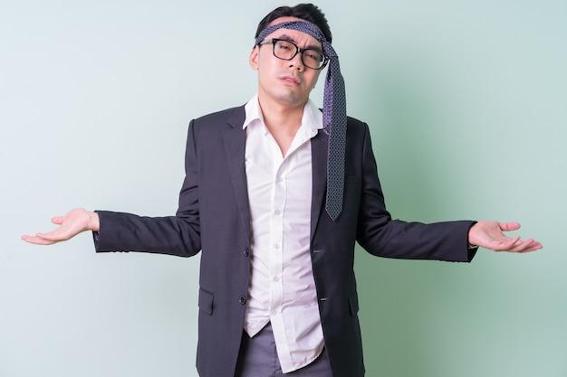 Młody azjatycki biznesmen pozuje na zielonym tle