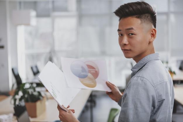 Młody azjatycki biznesmen pracuje przy biurem