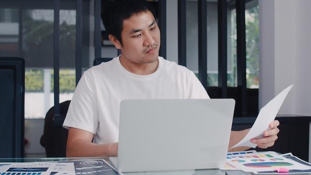 Młody azjatycki biznesmen rejestruje dochody i wydatki w domu. mężczyzna zmartwiony, poważny, stres podczas korzystania z rekordowego budżetu laptopa, podatków, dokumentów finansowych pracujących w salonie w domu.