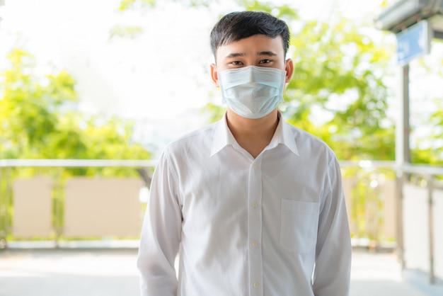 Młody azjatycki biznesmen w białej koszuli idzie do pracy w mieście zanieczyszczenia, nosi maskę ochronną, zapobiega pyłu pm2.5, smogowi, zanieczyszczeniu powietrza i covid-19 w bangkoku w tajlandii.