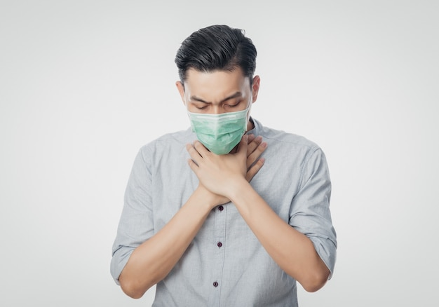 Młody azjatycki biznesmen w higienicznej masce cierpi ból gardła, koronawirusa. choroby układu oddechowego przenoszone drogą powietrzną, takie jak walka po południu i grypa. studio strzelający odizolowywającym na białym tle.