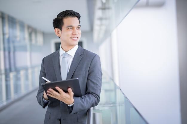 Młody azjatycki biznesowy mężczyzna trzyma pastylkę patrzeje daleko od