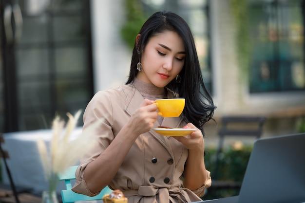 Młody azjatycki bizneswoman i niezależny siedzi na drewnianym stole