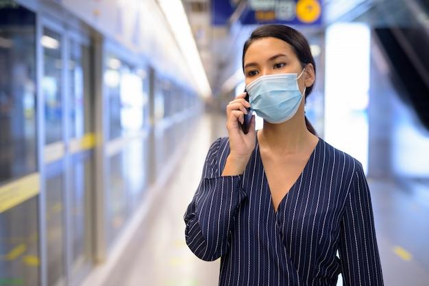 Młody azjatycki bizneswoman z maską opowiada na telefonie przy dworcem metra