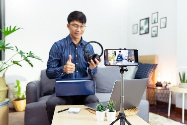 Młody azjatycki bloger nagrywający wideo vlog na aparacie recenzja produktu w domowym biurze, focus na zamontowanym na statywie ekranie aparatu transmituje transmisję wideo na żywo do sieci społecznościowej.