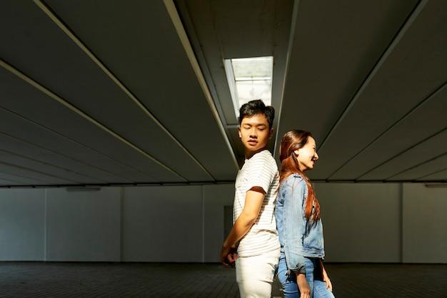 Młody azjatycki chłopak i dziewczyna stoją plecami do siebie podczas próby tańca w mediach społecznościowych