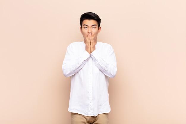 Młody azjatycki człowiek czuje się zmartwiony, zdenerwowany i przestraszony, zakrywający usta dłońmi, wyglądający na niespokojnego i zawalony na ścianie