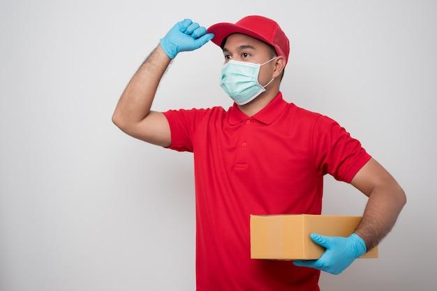 Młody azjatycki człowiek dostawy w mundurze na sobie maskę ochronną i gumowe rękawiczki