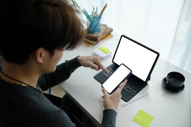 Młody azjatycki człowiek freelance siedzi w swoim miejscu pracy i przy użyciu telefonu komórkowego.