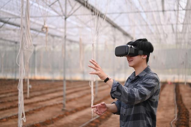 Młody azjatycki człowiek inteligentny rolnik stojący w szklarni i noszący technologię okularów rzeczywistości wizualnej.