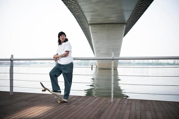 Młody azjatycki człowiek jeździ na deskorolce w mieście na zewnątrz