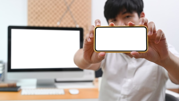 Młody azjatycki człowiek pokazuje inteligentny telefon z pustym ekranem.