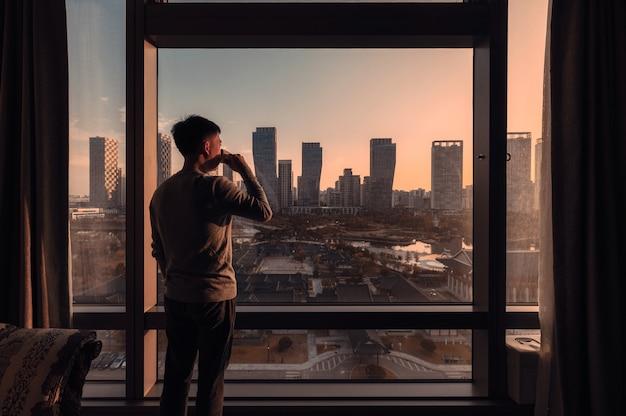 Młody azjatycki człowiek stojący z piciem kawy w hotelu