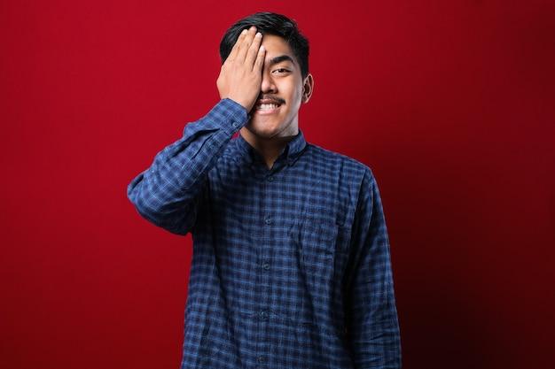 Młody azjatycki człowiek ubrany dorywczo flanelową koszulę zakrywającą jedno oko ręką, na czerwonym tle, pewny siebie uśmiech na twarzy i zaskoczenie emocji.