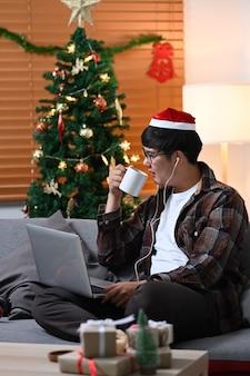 Młody azjatycki człowiek w santa hat picie gorących napojów i surfowanie po internecie z laptopa w domu.