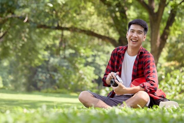 Młody azjatycki człowiek z plecakiem siedzi na trawie w letni dzień przystojny facet cieszyć się stylem życia na świeżym powietrzu na wakacyjnych wakacjach