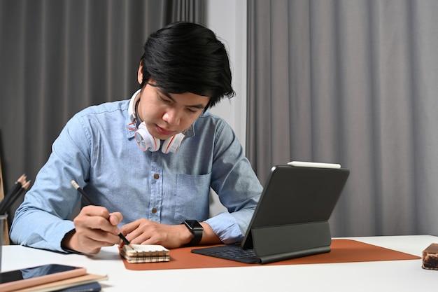Młody azjatycki człowiek z słuchawki siedzi w domowym biurze i pracuje z tabletem komputera.