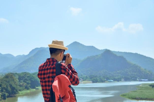 Młody azjatycki fotograf podróżniczy robi zdjęcia na zewnątrz