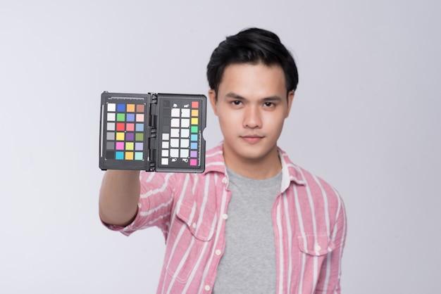 Młody azjatycki fotograf trzymający kartę sprawdzania kolorów podczas pracy w studio
