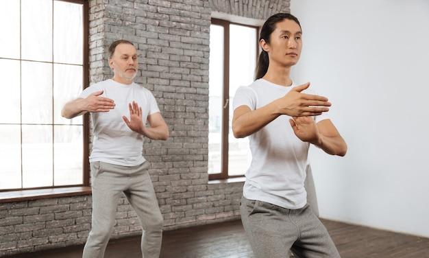 Młody azjatycki instruktor ubrany w białą koszulkę, trzymając zgięte ramiona, pokazując swojemu gościowi ćwiczenia