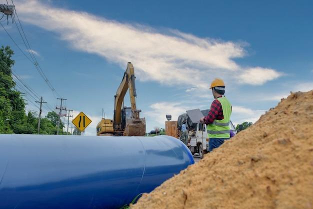 Młody azjatycki inżynier przegląda duży kanał na placu budowy