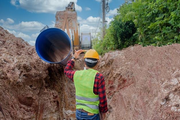 Młody azjatycki inżynier sprawdza duży kanał ściekowy zakopany pod ziemią na placu budowy