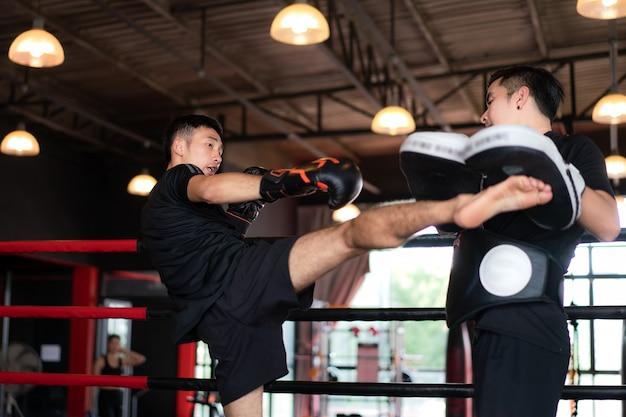 Młody azjatycki kick bokser kopiąc profesjonalnego trenera na stadionie bokserskim
