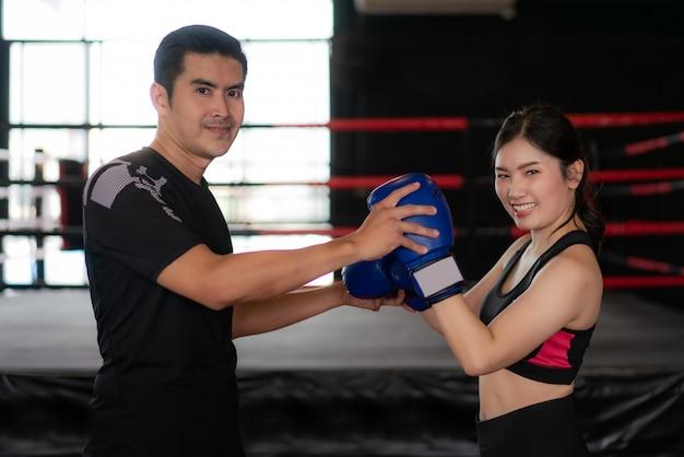 Młody azjatycki kobieta bokser z profesjonalną trener pozą i ono uśmiecha się przy kamerą podczas trainning.