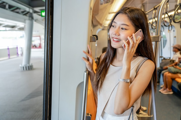 Młody azjatycki kobieta pasażer robi rozmowie telefonicza przez mądrze telefonu komórkowego w metrze podczas podróży w dużym mieście