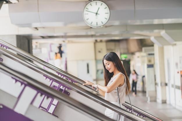 Młody azjatycki kobieta pasażer używa mądrze telefon komórkowego i chodzący w górę schodków w staci metru