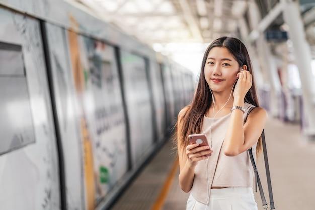 Młody azjatycki kobieta pasażer używa muzykę i słucha