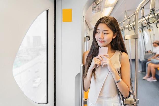Młody azjatycki kobieta pasażer używa ogólnospołeczną sieć przez mądrze telefonu komórkowego w metra trai