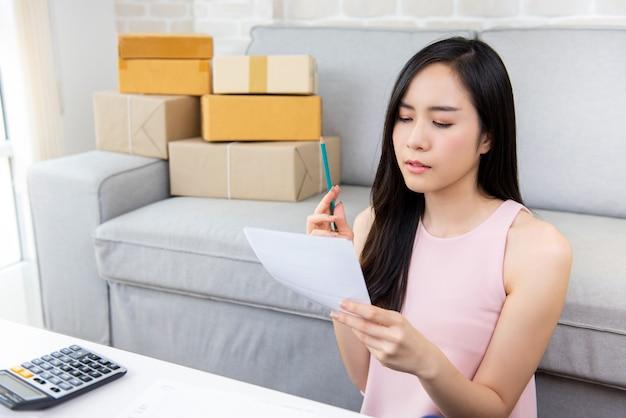 Młody azjatycki kobieta przedsiębiorca lub freelance online sprzedawca sprawdza rozkazy w domu