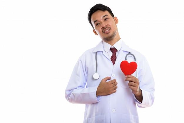 Młody azjatycki lekarz człowiek trzyma czerwone serce podczas thouching serca