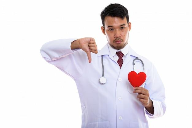 Młody azjatycki lekarz mężczyzna trzyma czerwone serce i daje kciuk w dół