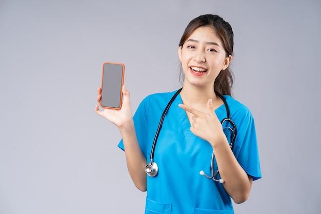 Młody azjatycki lekarz z smartphone na szaro