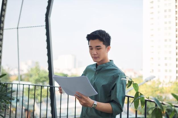 Młody azjatycki mężczyzna czytający dokumenty, stojący na balkonie na zewnątrz