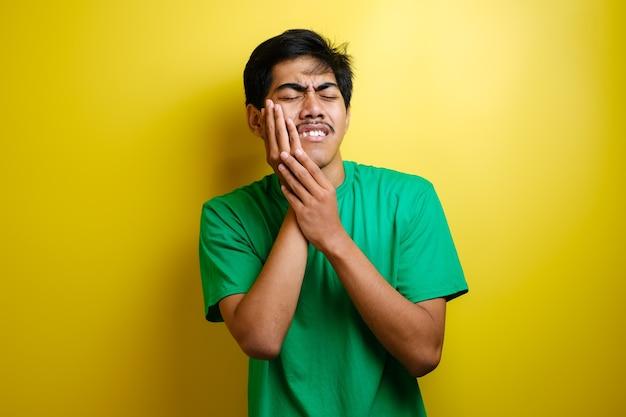Młody azjatycki mężczyzna dotykający szczęki, mający silny ból, koncepcja bólu zęba na żółtym tle