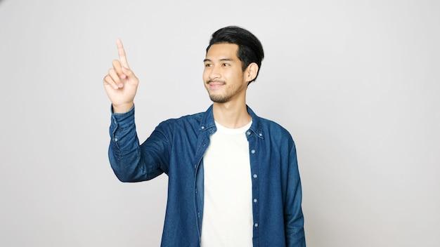 Młody azjatycki mężczyzna handpoint uśmiecha się, stojąc nad odosobnionym szarym tłem