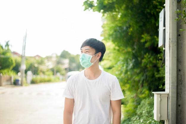 Młody azjatycki mężczyzna jest ubranym maskę w mieście plenerowym
