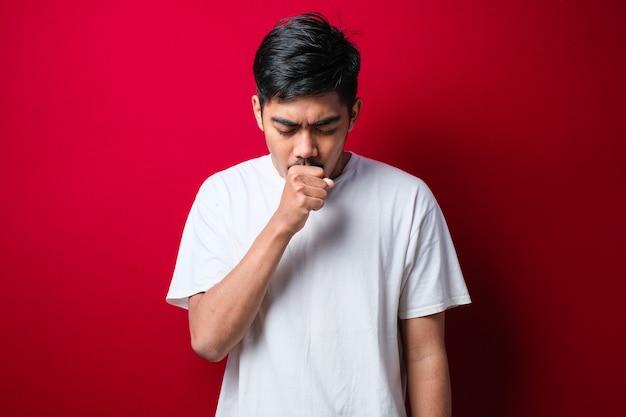 Młody azjatycki mężczyzna kaszle z bólem gardła, koncepcja człowieka z alergią na czerwonym tle