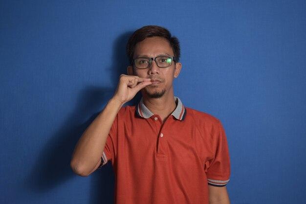 Młody azjatycki mężczyzna na niebieskim tle usta i usta zamknięte jak zamek z palcami tajne i ciche