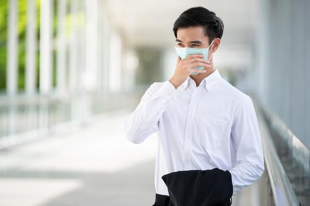 Młody azjatycki mężczyzna nosi medyczną maskę ochronną do ochrony koronawirusa, covid-19 i pm2,5 w mieście