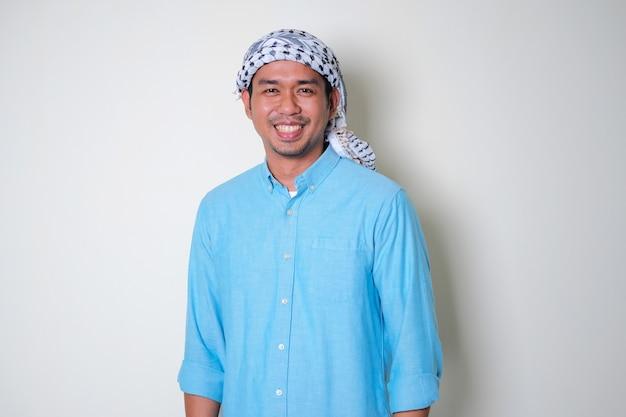 Młody azjatycki mężczyzna noszący arabski szalik shemagh uśmiechający się przyjaźnie