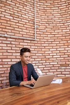 Młody azjatycki mężczyzna obsiadanie przy drewnianym stołem, działanie na laptopie i ściana z cegieł w tle